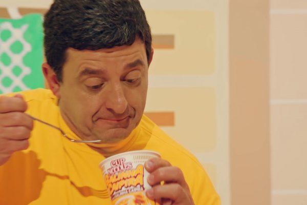 homem de camiseta amarela segurando um garfo para comer cup noodles estrelando uma campanha de marketing agressivo