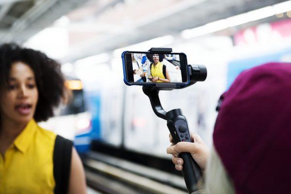mulher jovem adulta e micro influenciadora no metro gravando um vídeo para suas redes sociais