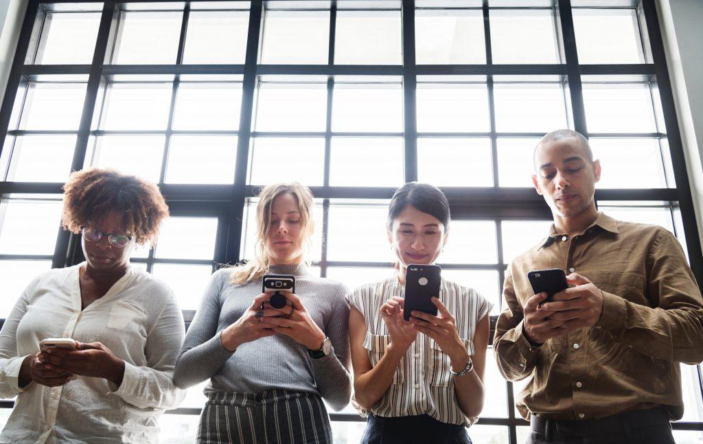 quatro-pessoas-segurando-celular-e-navegando-na-internet-observando-fim-dos-likes
