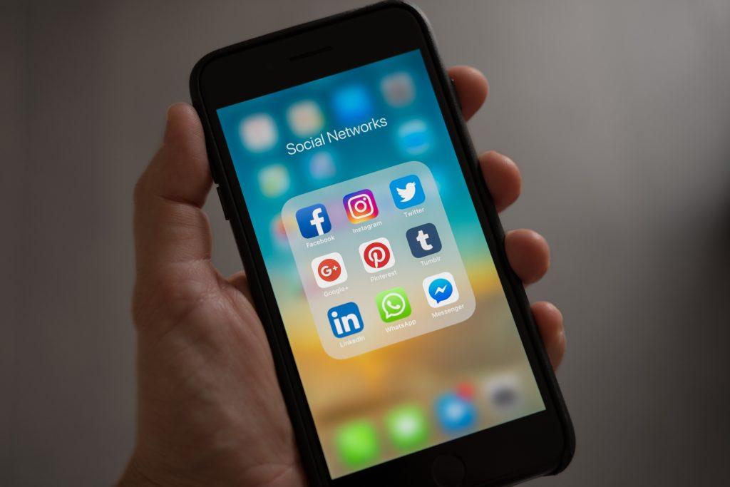 mão segurando iphone desbloqueado com tela mostrando pastas com ícones de redes sociais