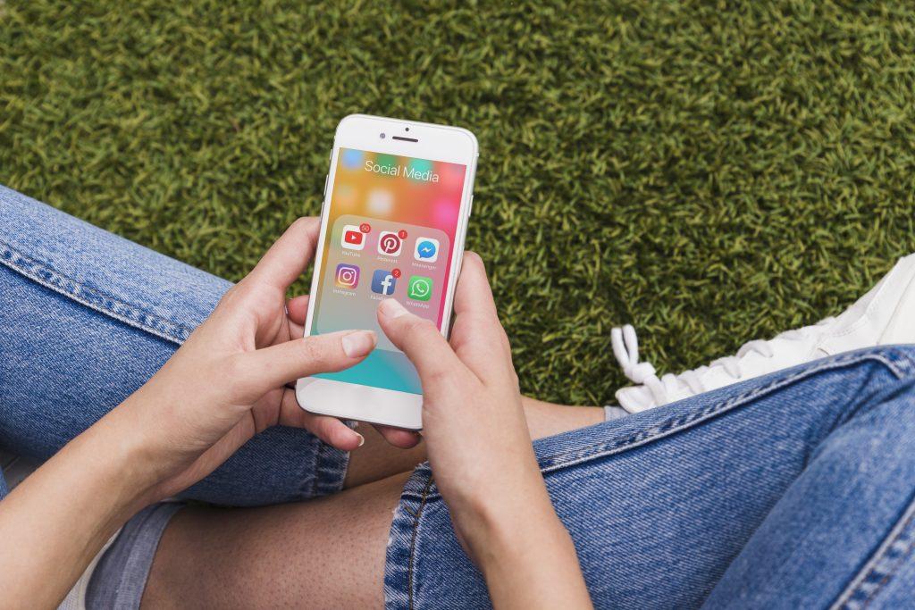 Tela de celular com redes sociais, texto sobre Social Ads